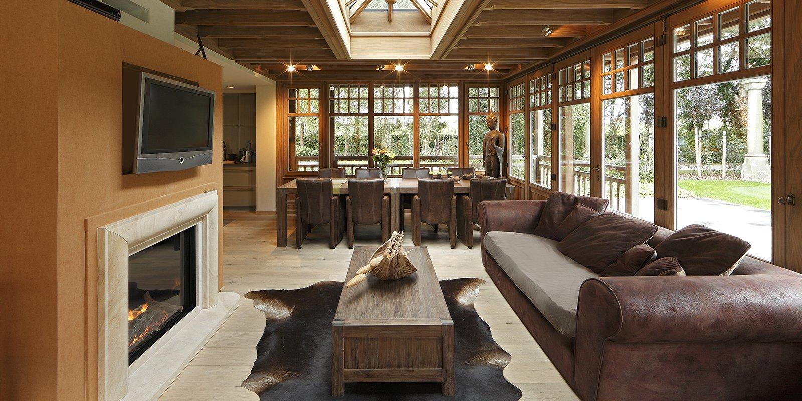 Landelijke woonkamer met een M-Design haard, inrichting schilder en behang werken door Decoratiebedrijf Maes en een houten vloer van Parket Vermeersch