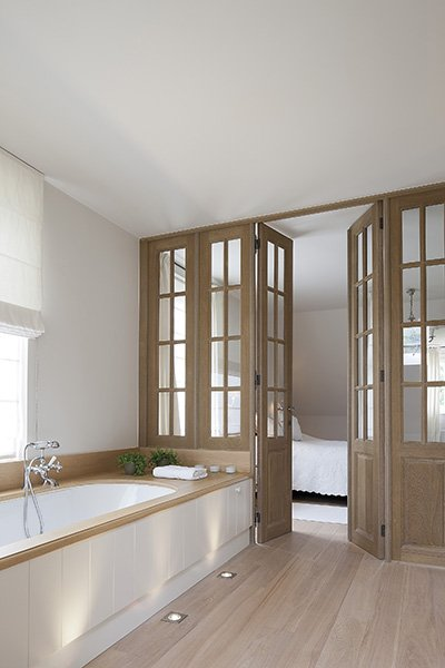 Scheiding tussen badkamer en slaapkamer door middel van deuren, ontworpen door b+villas in een landelijke stijl
