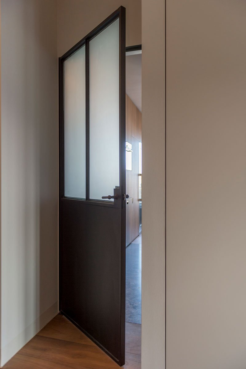 Stalen pivotdeur tussen keuken en hal van SteMat, Klassiek & Romantisch, Bernard de Clerck