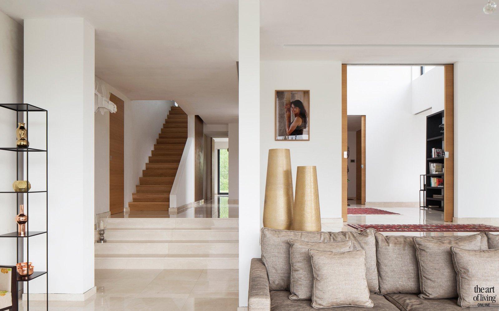 zicht vanuit de woonkamer op de hal met houten trap