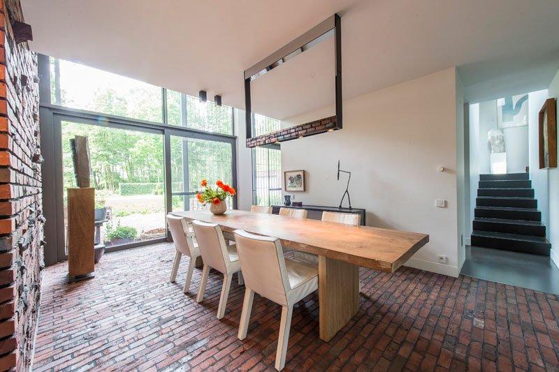 Houten eettafel, zicht op de tuin, grote ramen door Simons deuren en ramen, contrast met rode baksteen, BVV Architecten, hedendaagse villa