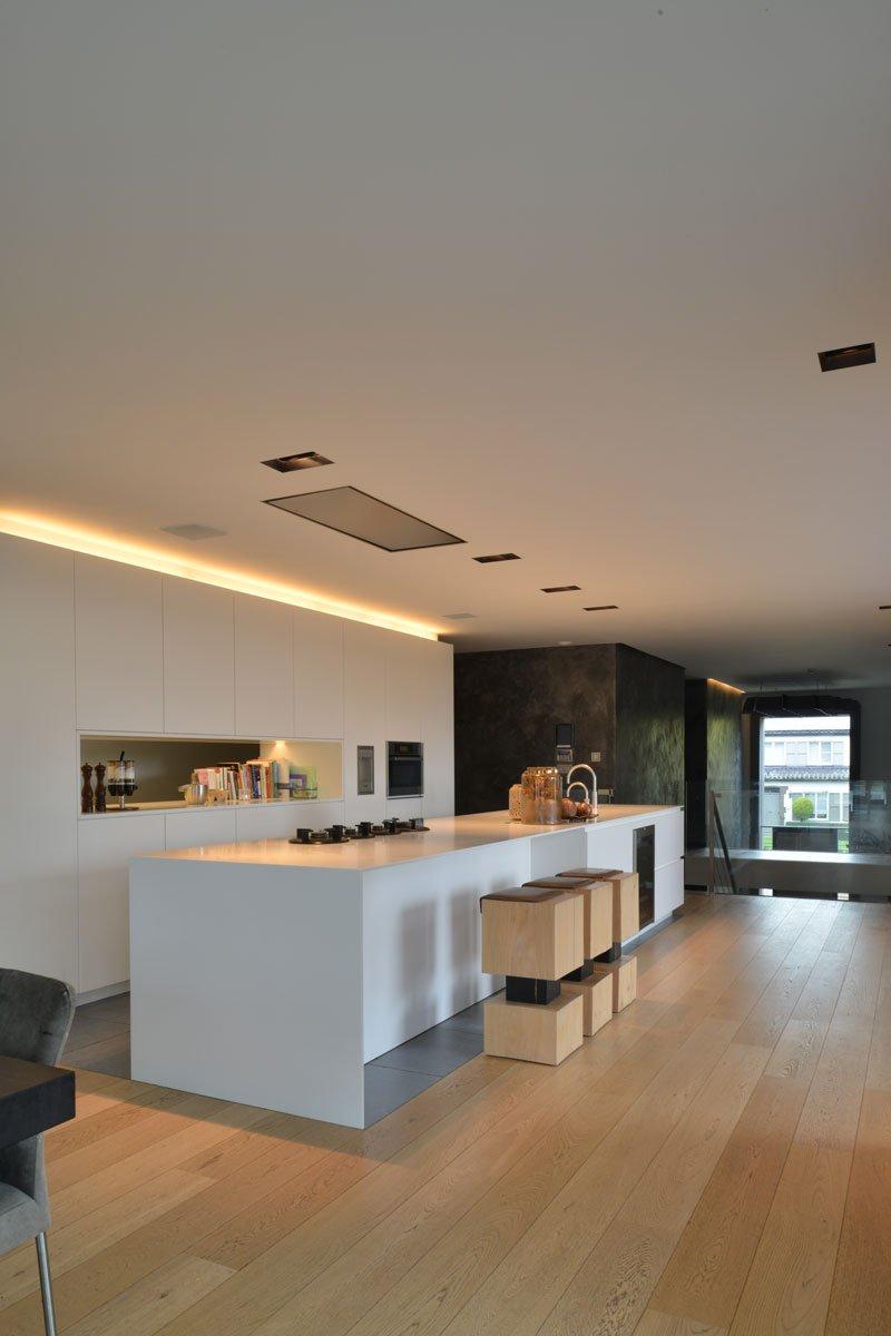 Maatwerk keuken, Vado Keukens, strake witte keuken, open verbinding, houten krukjes, houten vloer, moderne villa, VVR Architecten