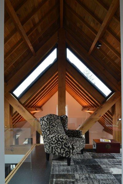 Bovenverdieping, houten balken, lounge stoel, comfortabel, natuurlijke materialen, modern gastenverblijf, VVR Architecten