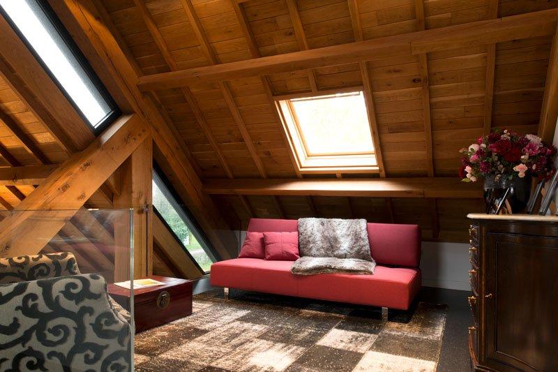 Bovenverdieping, dakraam, rode bank, houten balken, modern gastenverblijf, VVR Architecten