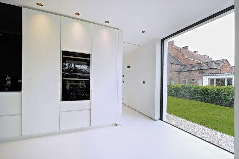 Strakke, witte keuken, Interioo, maatwerk, contrast, gietvloer, grote ramen, Yvo Boven