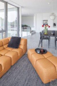 Ruime woonkamer, kleurrijk meubilair, neutraal interieur, grijze tegels, zwarte eettafel, villa in L-vorm, p.ed architecten