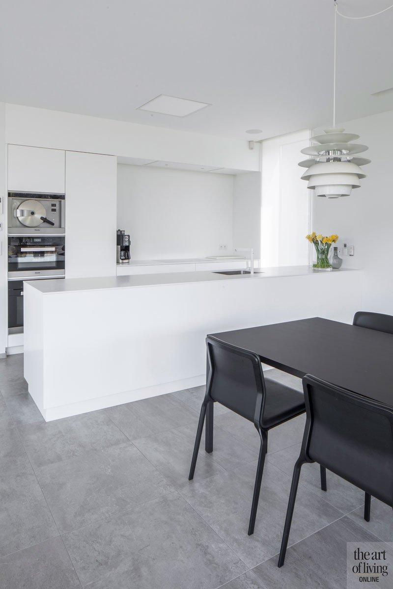 Strakke keuken, wit, neutrale kleuren, grijze tegelvloer, eettafel, villa in L-vorm, p.ed architecten