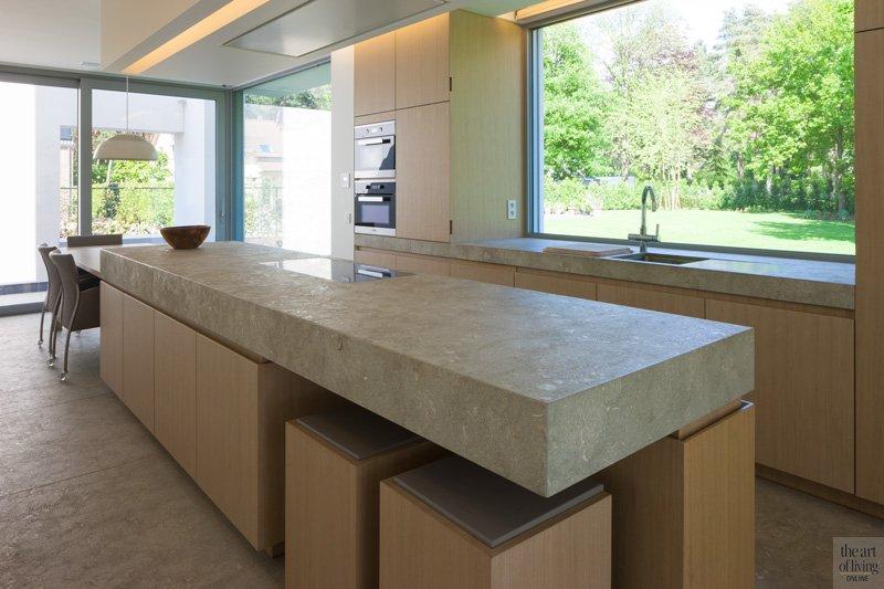 Keuken, natuursteen, Mediterranean Green, G&M Natural Stones, breed raam, zicht op de tuin, houten tafel, houten kastjes, zelfvoorzienende villa, Anja Vissers