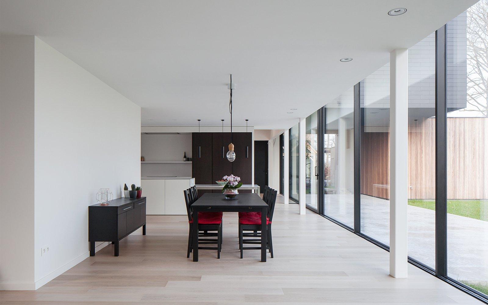 Woonkamer, houten vloer, grote ramen, lichtinval, eettafel, sfeervolle woning, Hulpia Architecten