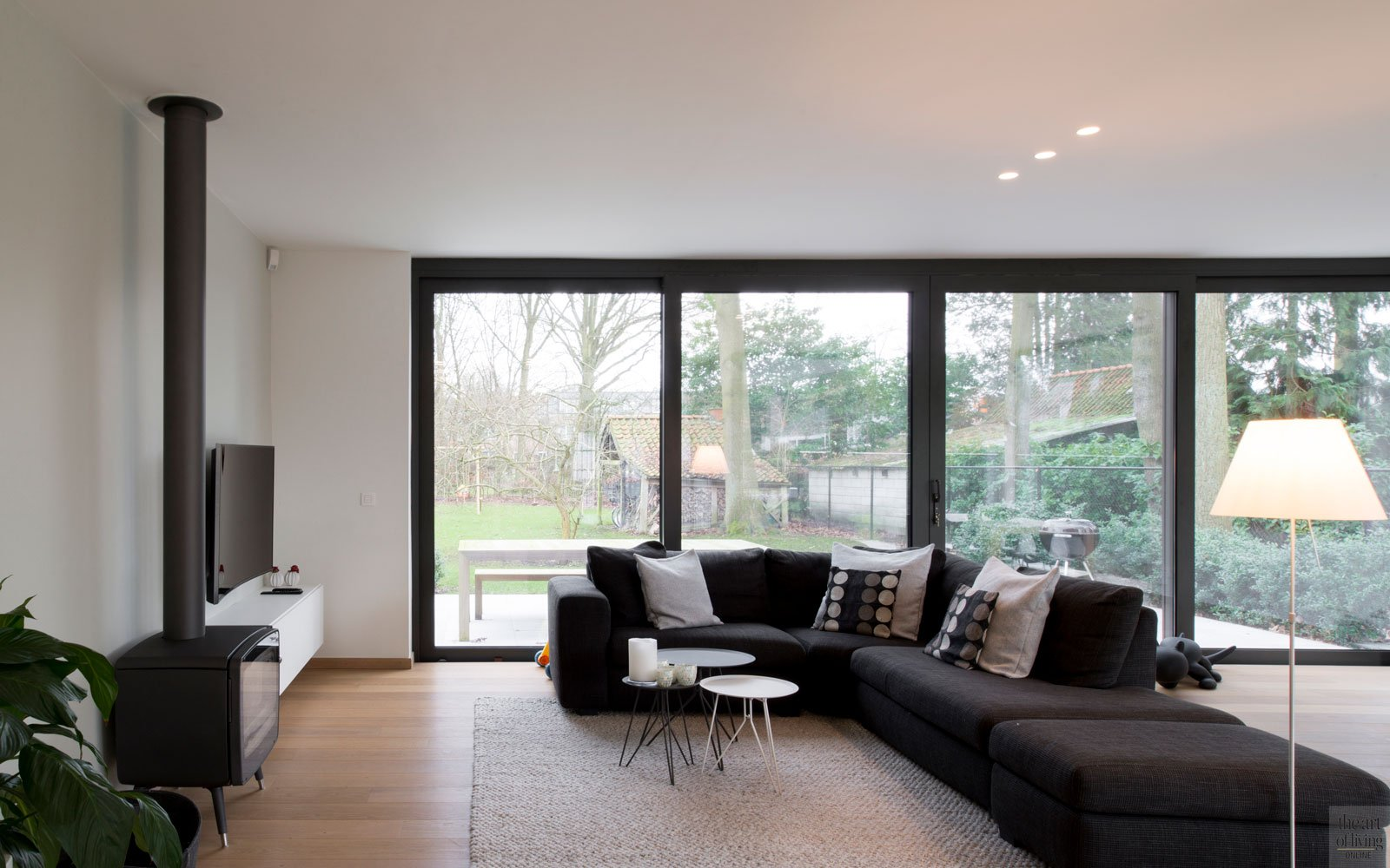 Woonkamer, kachel, hoekbank, grote ramen, houten vloer, living, moderne villa, Leers & Partners